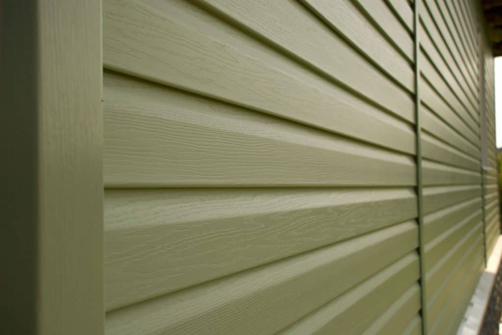 An up close photo of a green wooden siding