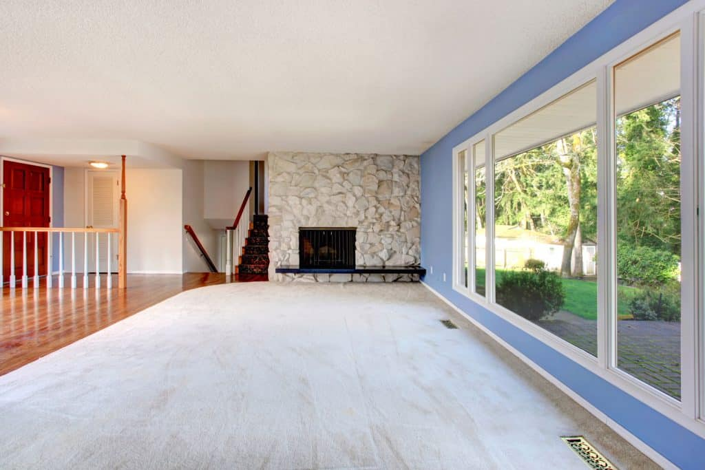 Awesome blue spacious living room with a huge window on the right side and a fireplace on the background