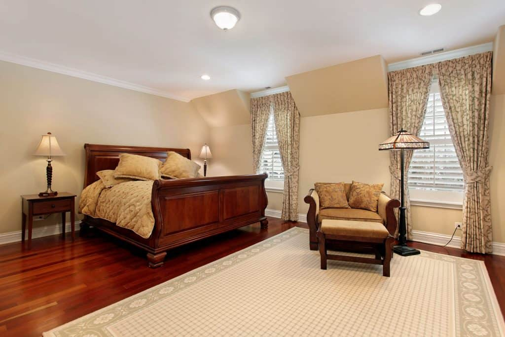 Bedroom incorporated with a vintage style, a craftsman made bed, hardwood flooring, white rug, and cream colored walls