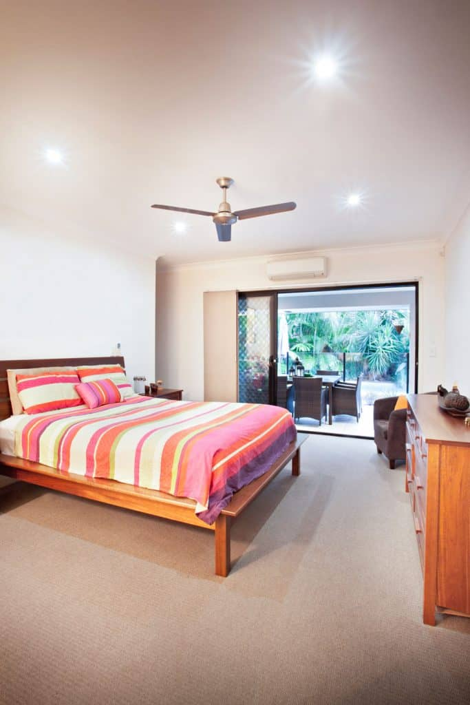 Bedroom with a contemporary design with white walls, carpeted floor, and brown wooden furnitures