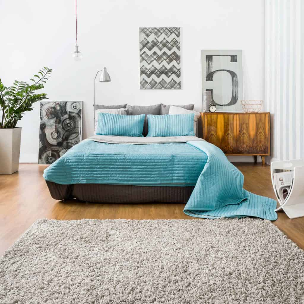 Bedroom with wooden laminated flooring, blue beddings, a wooden nightstand, and a gray rug on the floor