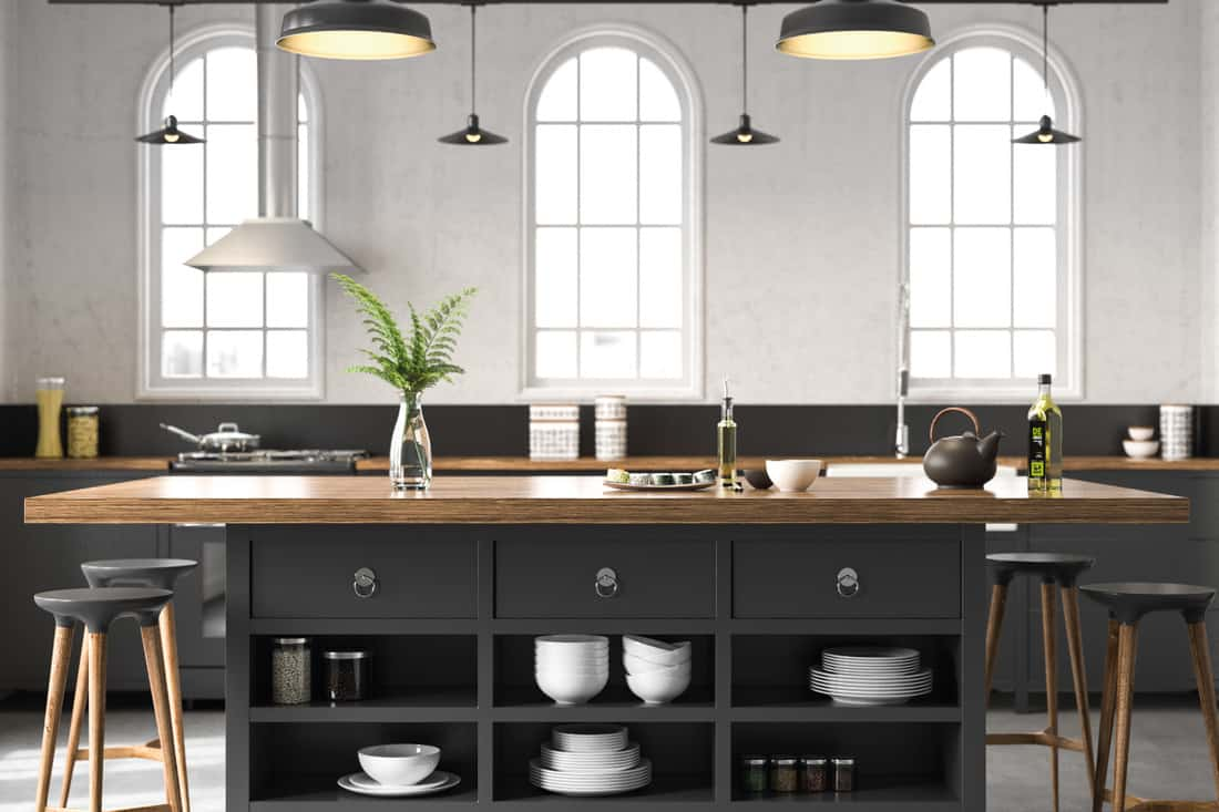 Black industrial kitchen with gray flooring and wooden chair stools