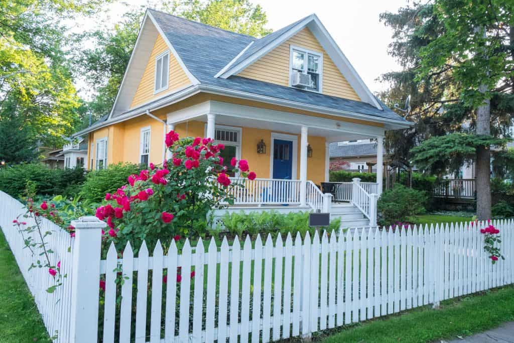 Classic colonial house with light yellow painted walls and white painted fence