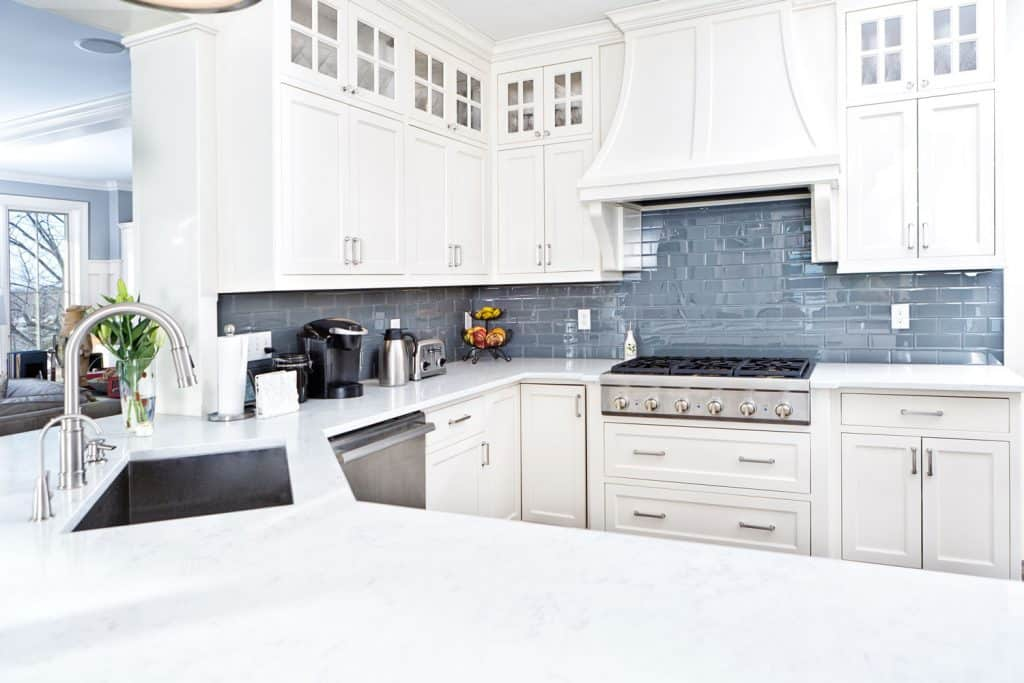 Classic kitchen with white wooden panels, blue brick patterned and a range hood