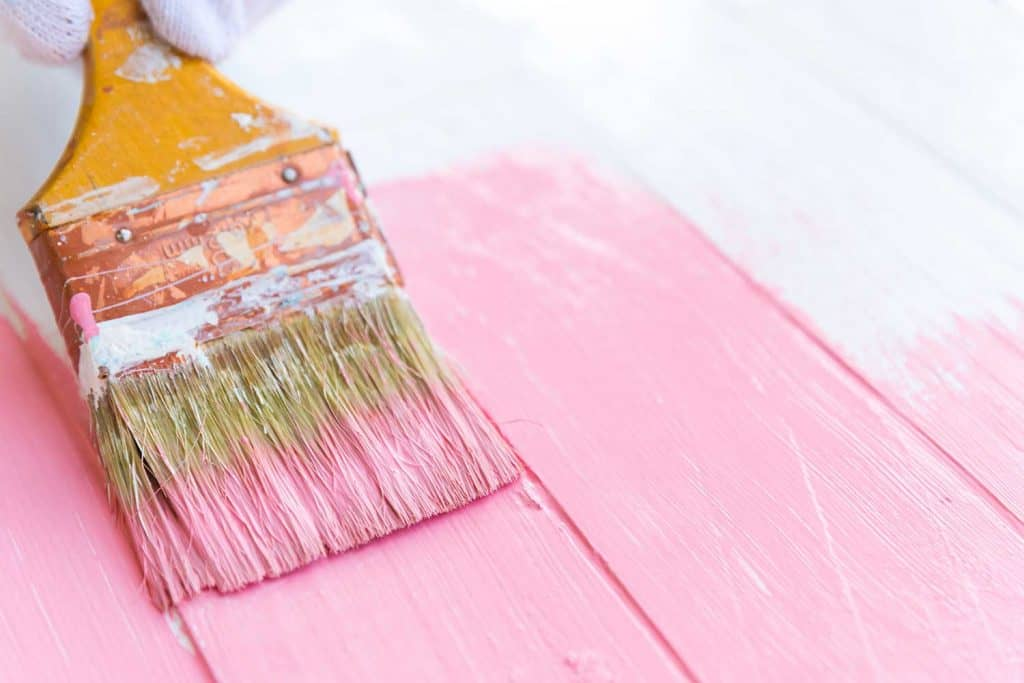 Close up of a woman hand holding brush painting pink color on a white wooden table