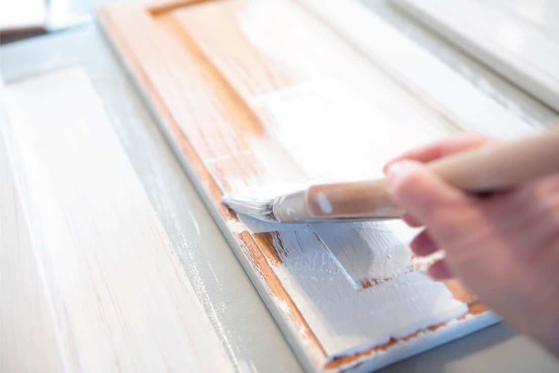 Close up of hand painting kitchen cabinets with white paint