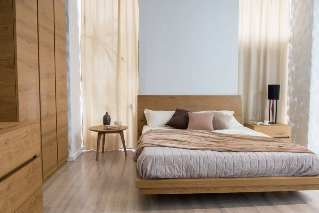 Contemporary designed bedroom with wooden cabinets, concrete header wall, wooden bed and white beddings with gray bedsheets