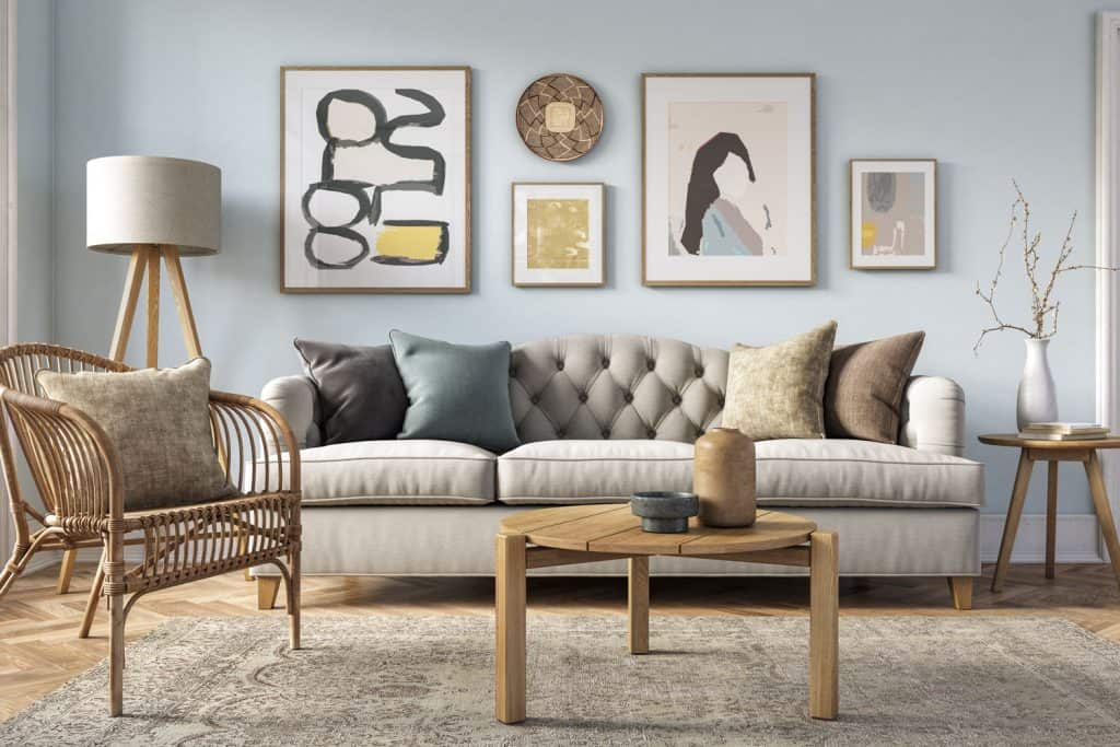 Country inspired living room aesthetics with a round wooden coffee table, rattan chair, and a gray sleeper sofa