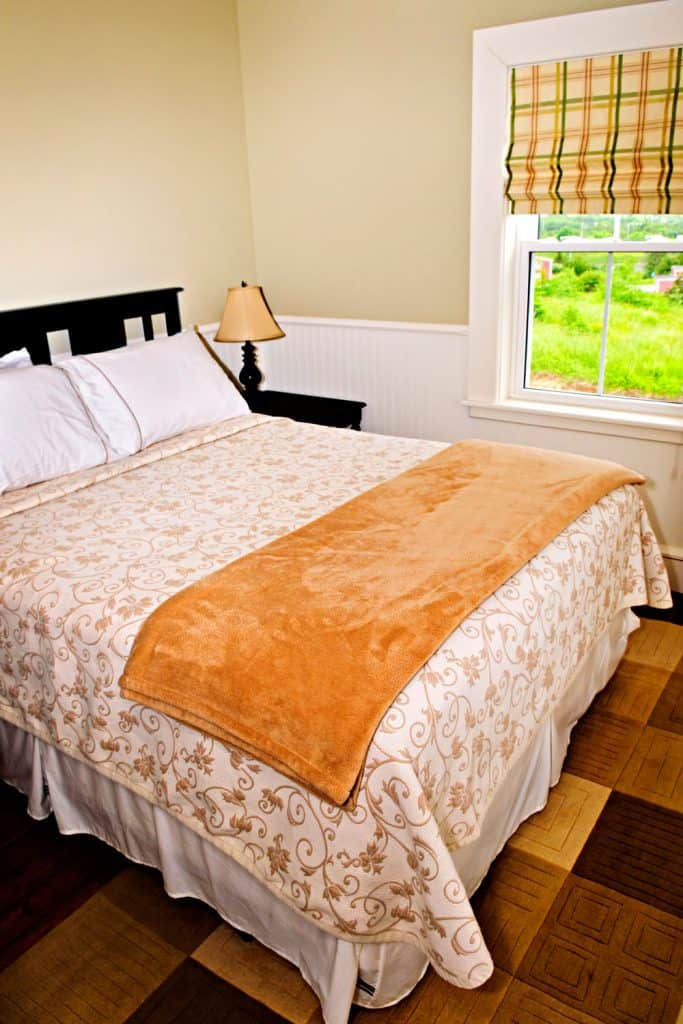 Cream painted bedroom with floral beddings and a brown patterned flooring