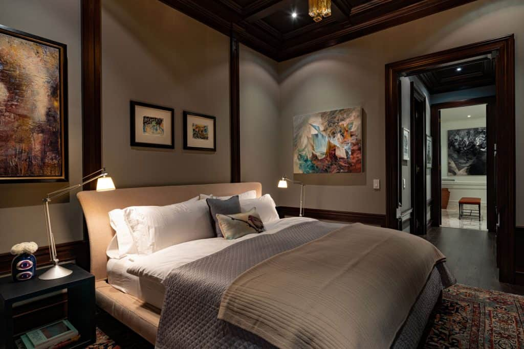 Dark contemporary themed bedroom with brown painted walls, comfortable bed with dark bedsheets, and white pillows with white beddings
