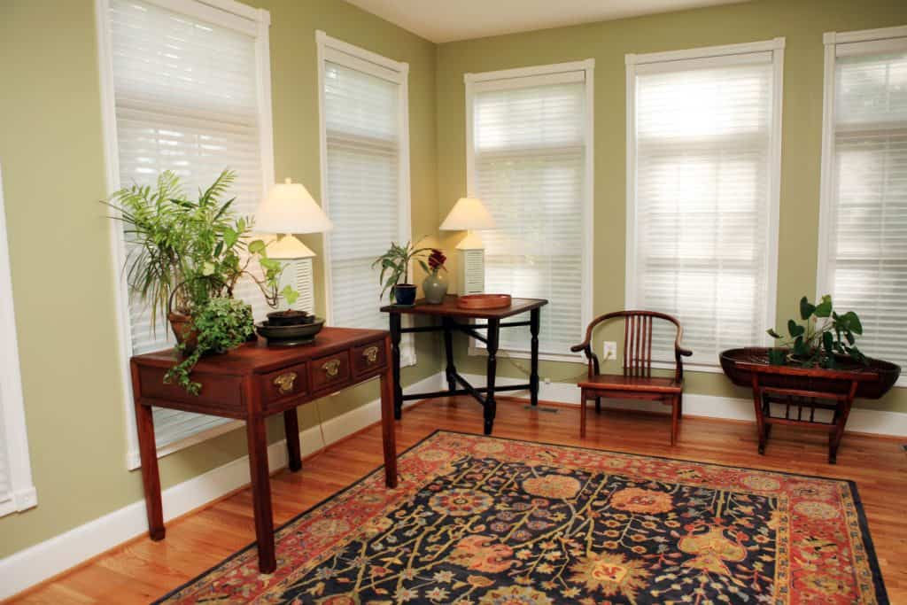 End tables, small wooden chair, laminated flooring with a floral rug, and light green walls and windows