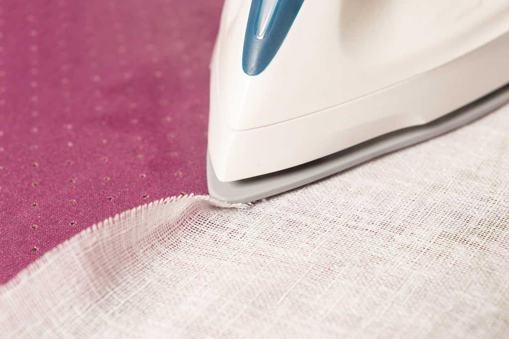 Fabric curtain being ironed on pink carpet as background