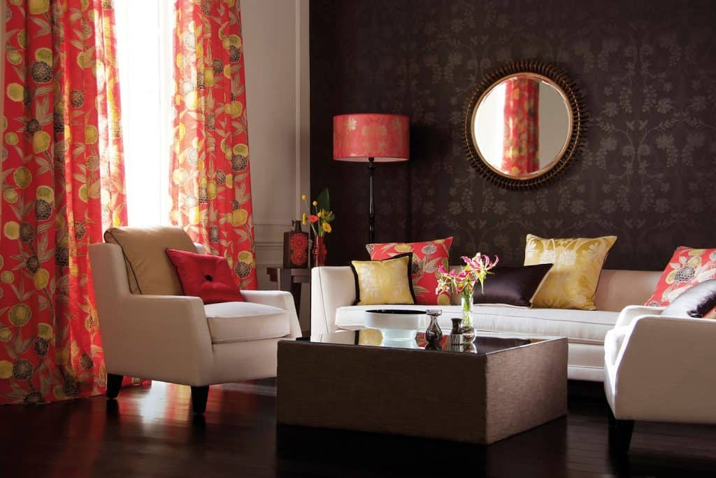 Gorgeous dark themed living room with light colored sofas with throw pillows on it, and floral red curtains