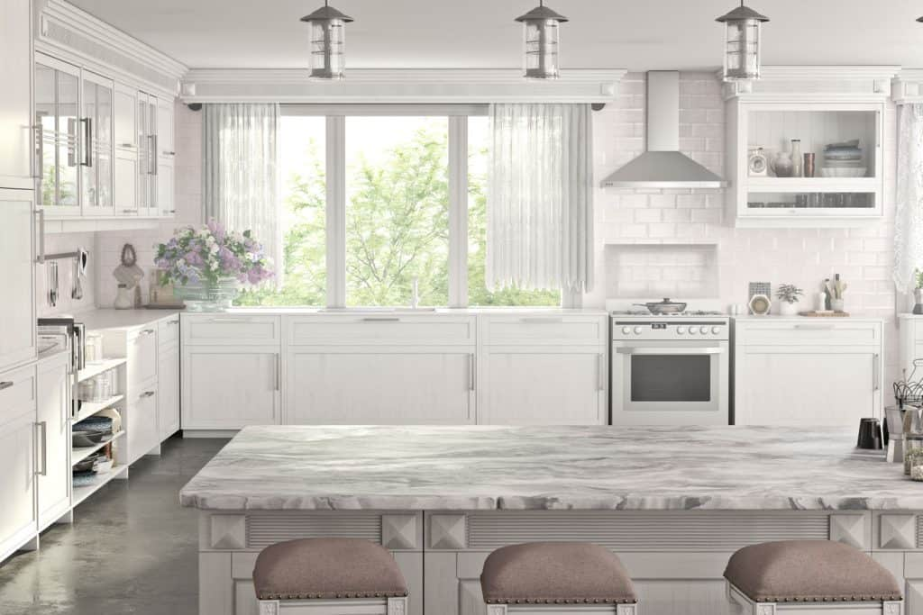 Gorgeous kitchen with a kitchen island made from white marble and wooden paneled cabinets