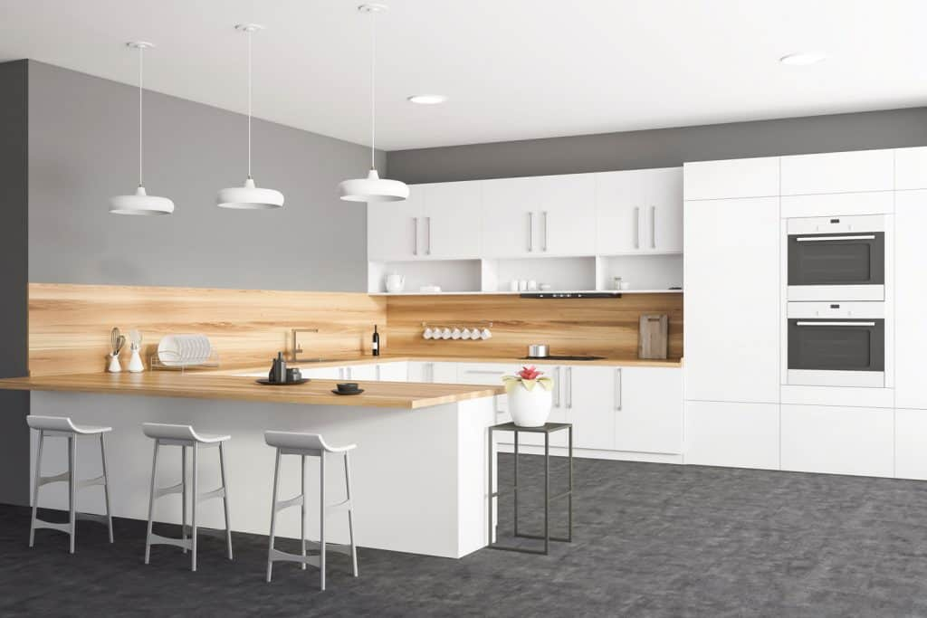 Gorgeous modern contemporary kitchen with a wooden backsplash, white cabinet panels and gray flooring