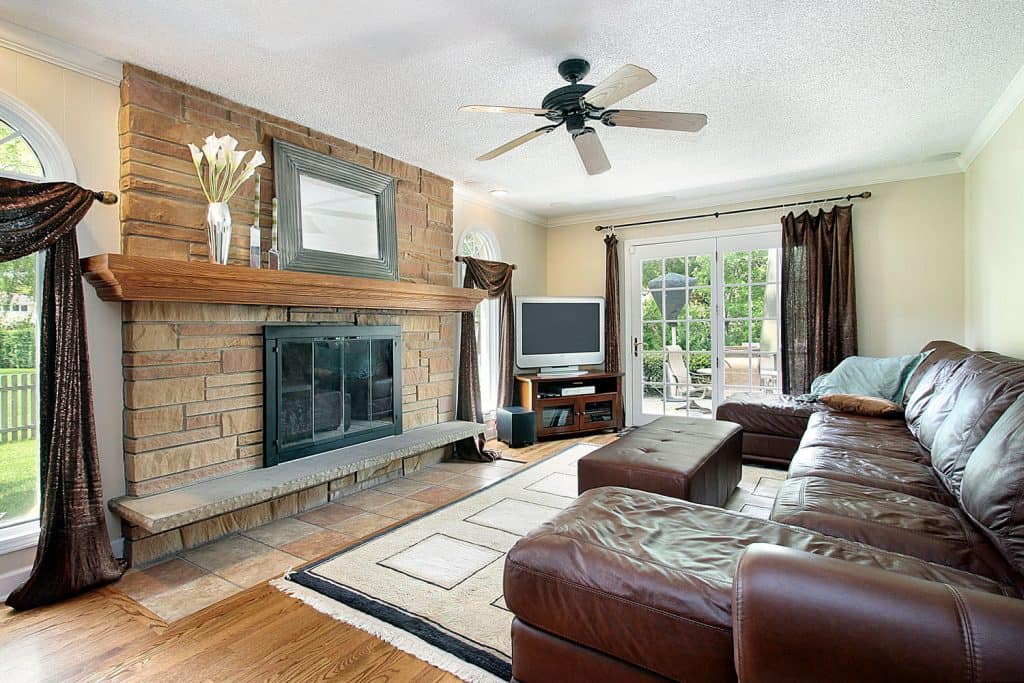 Gorgeous modern country styled living room with brown sofas, ottoman and a TV with large brick accent wall