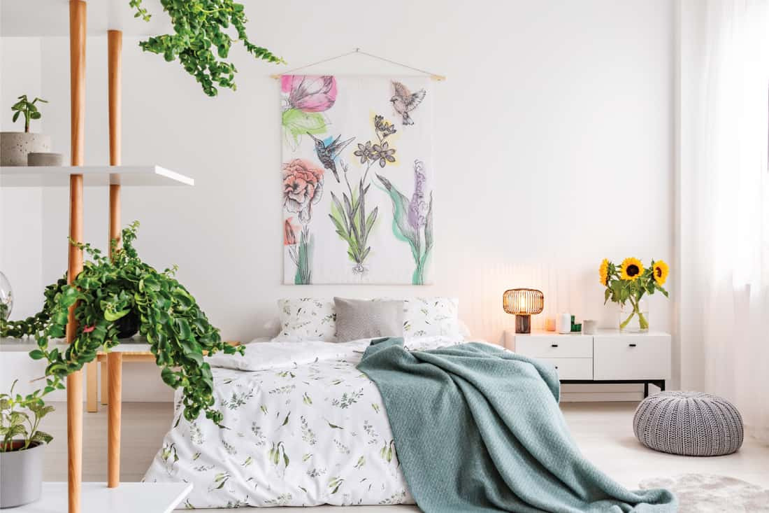 Green plants on shelves beside a bed dressed in white cotton bedding and teal blue blanket, artsy canvas hanging on the wall