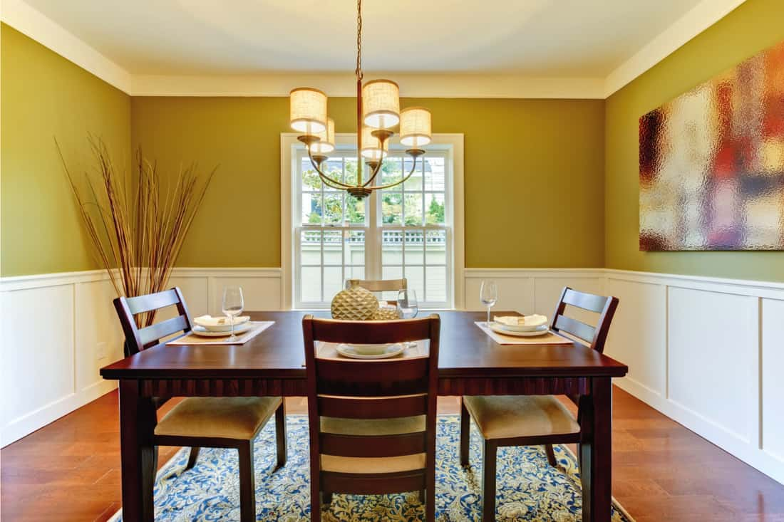 Green walls in large dining room with cherry floor