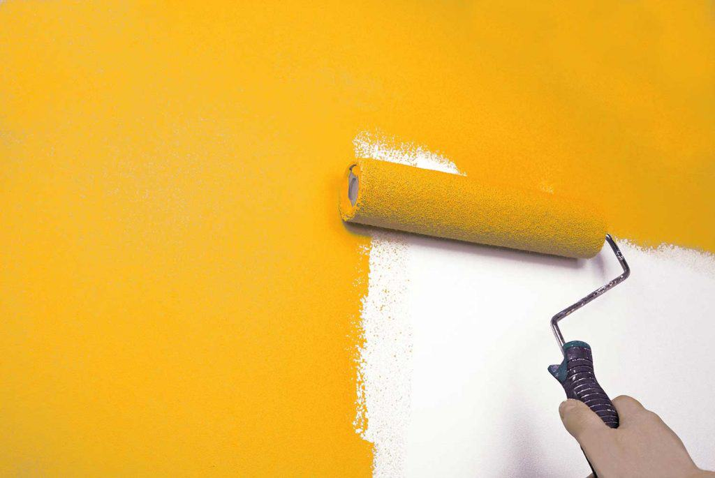 Hand painting wall using paint rollers