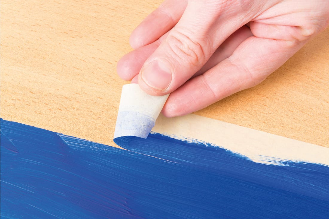Hand removing masking tape also known as sticky tape