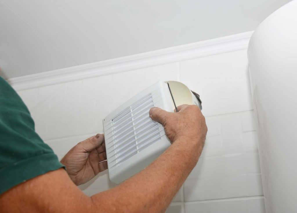 Handyman installing new bath vent fan