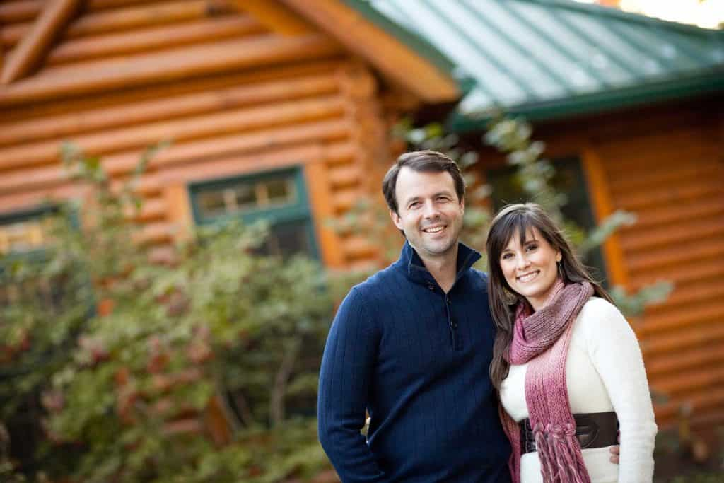 Happy couple standing together outside of a log house