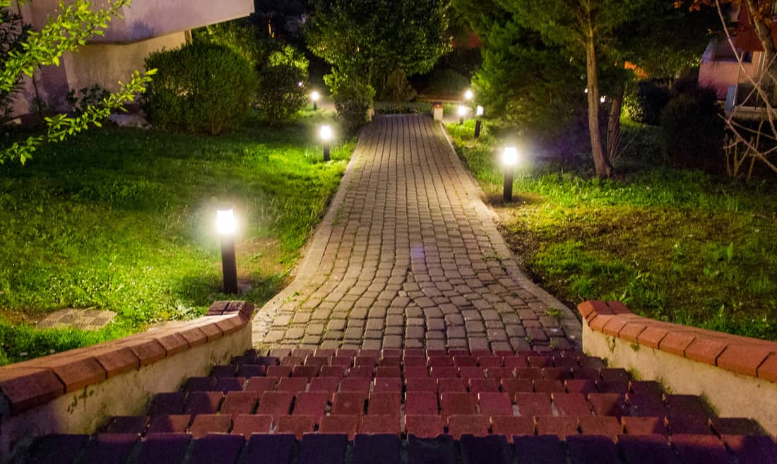 House and garden with path lights in city at midnight