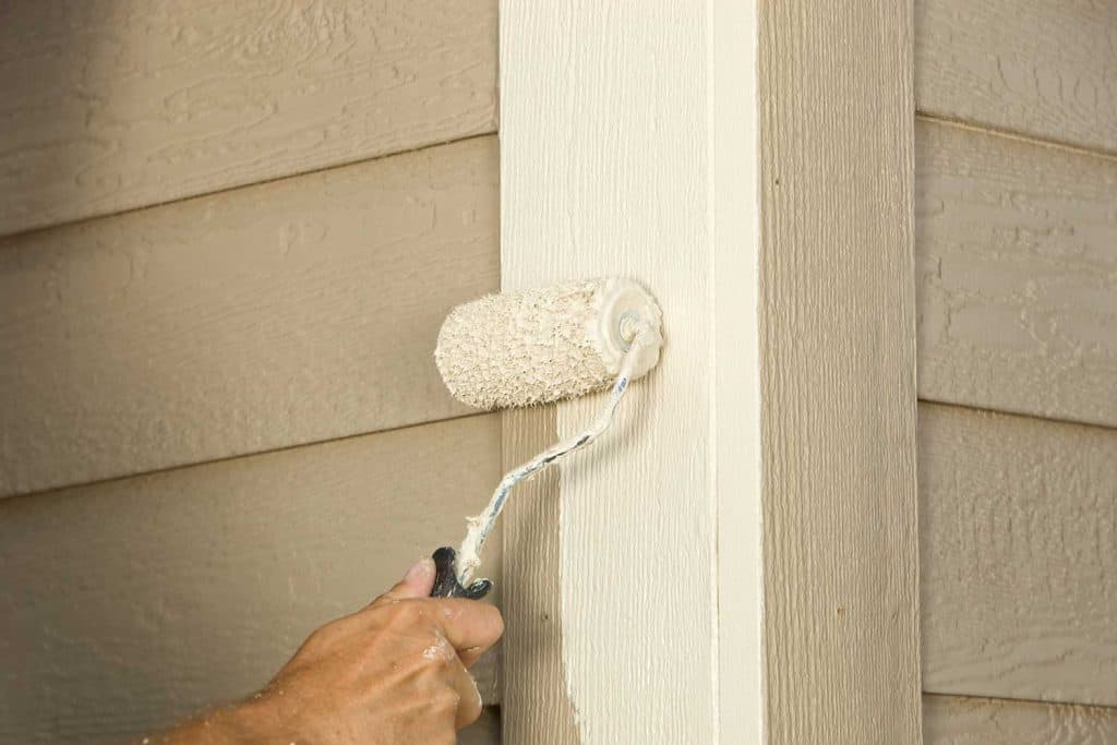 House painter rolling siding trim board