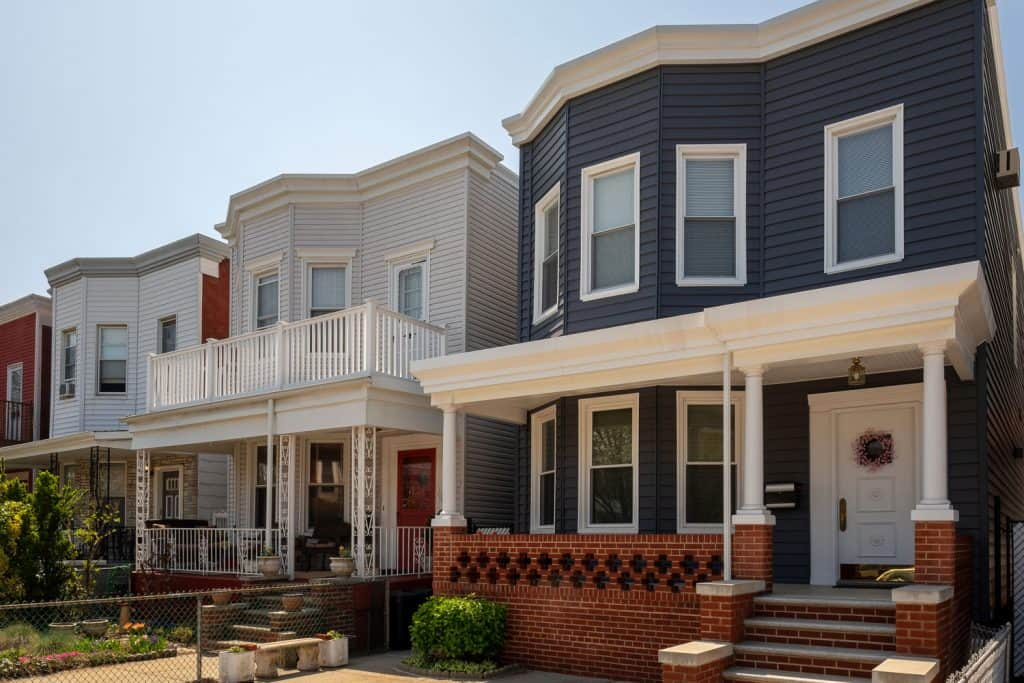 Rows of housing with wooden white and blue painted sidings, bay windows, and a small gorgeous porch