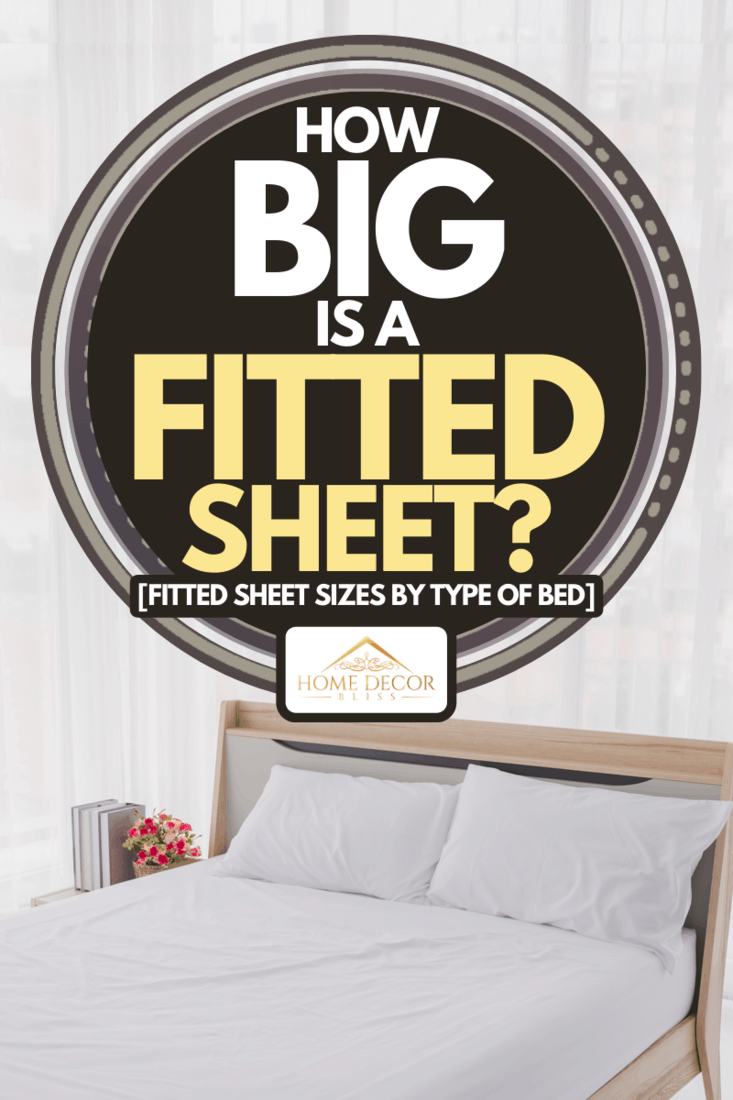 A modern bedroom interior with clean white bed and pillows, How Big is a Fitted Sheet? [Fitted Sheet Sizes by Type of Bed]