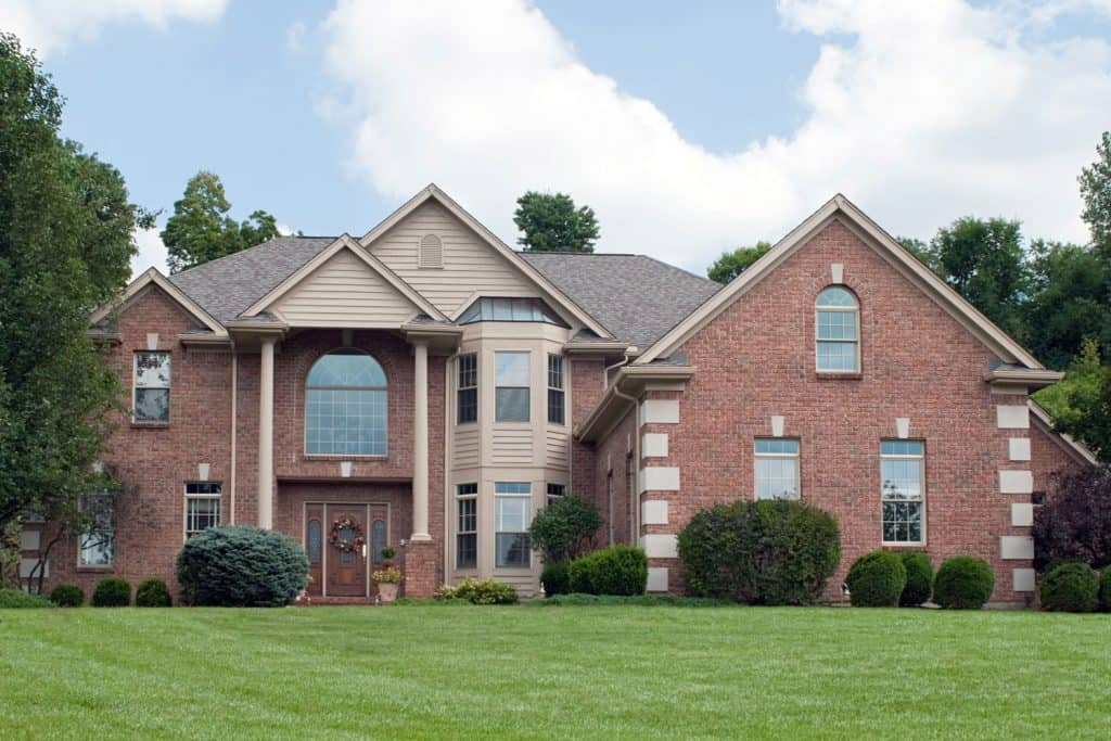Huge majestic country brick made mansion, cream painted wooden sidings on the bay window section, and asphalt roofing