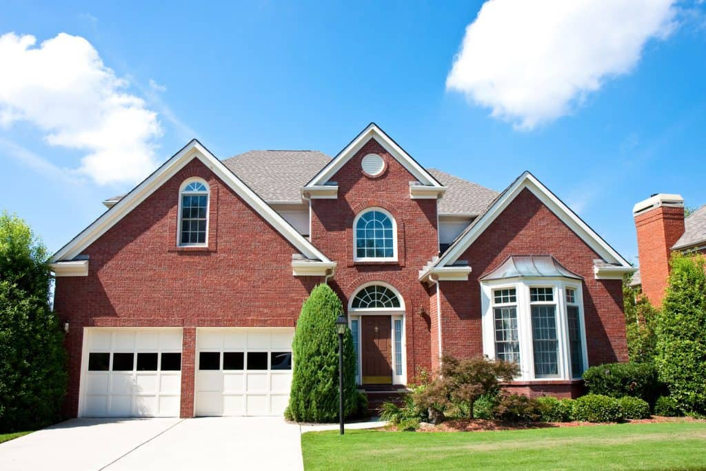 Huge red brick mansion with pointed roofing installed with shingles and a two car garage