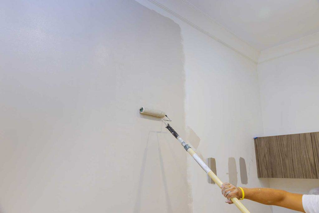 Industrial worker using roller to paint walls