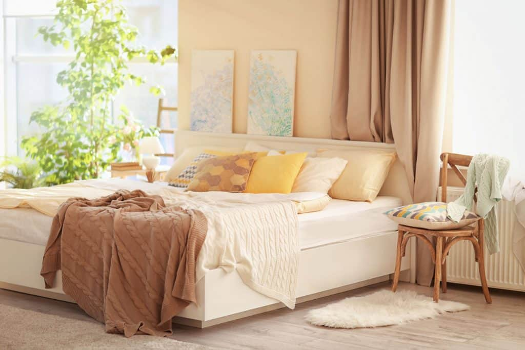 Interior of a modern bedroom with unfolded bed sheets, a cream colored bed, and an indoor plant on the background