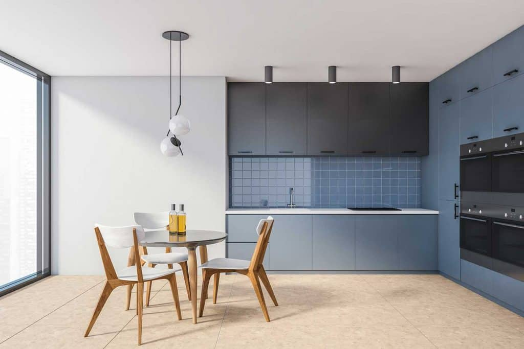 Interior of stylish kitchen with white and blue walls, tiled floor, blue cabinets with built in items and round dining table with chairs
