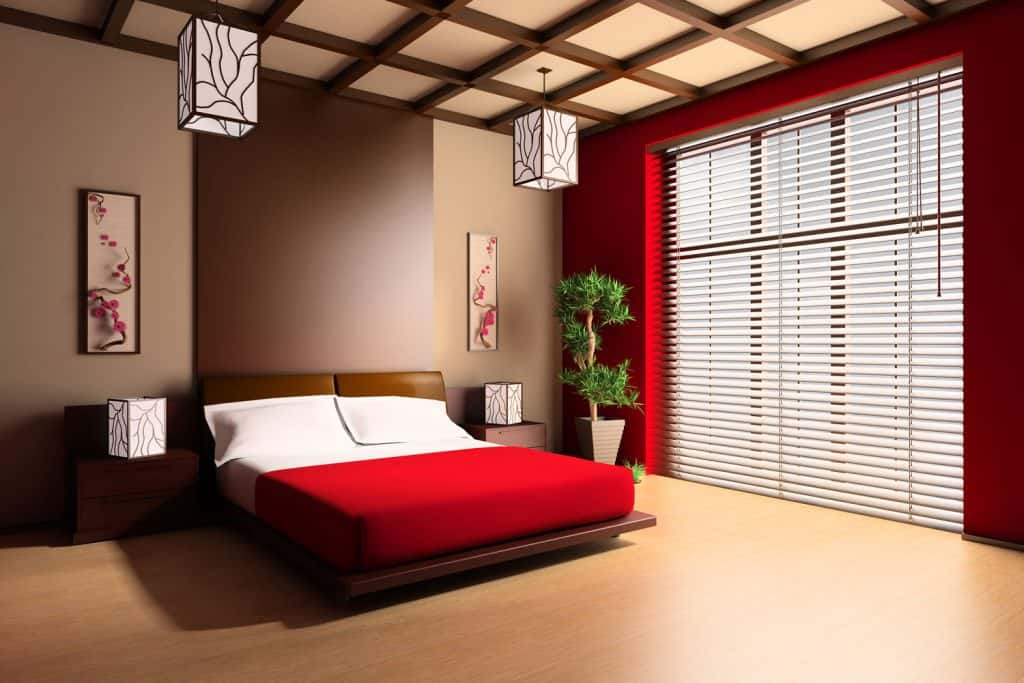Japanese inspired bedroom with brown walls, brown flooring, white beddings with red bedsheets, and brown furnitures