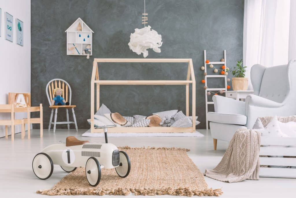 Kids playroom with gray accent wall, white walls, white flooring with toys and a white accent chair