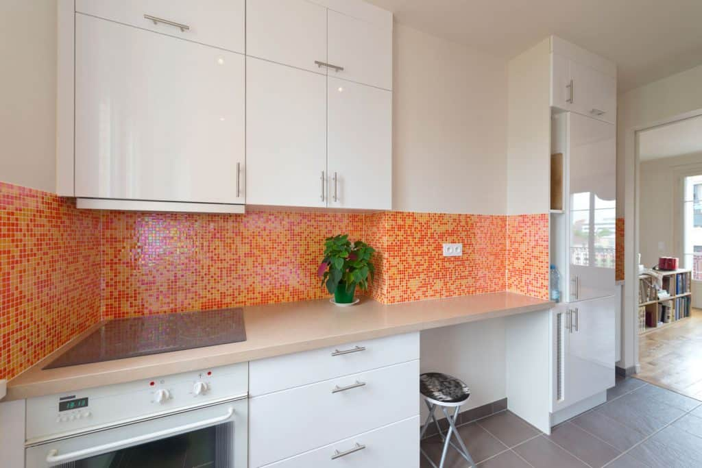 Kitchen with white cabinet panels light red backsplash and gray tiled flooring