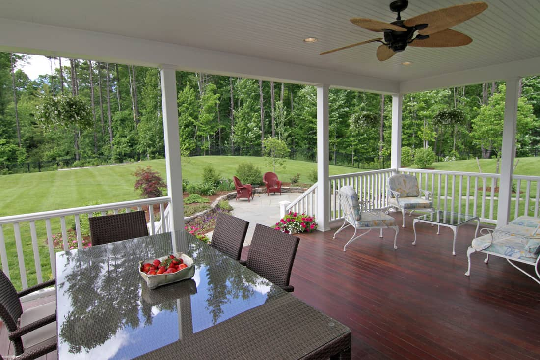 Large deck with outdoor ceiling fan for entertaining with ceiling fan and overhead lighting, leading to landscaped stone patio and garden with rolling lawn and backed up by forest