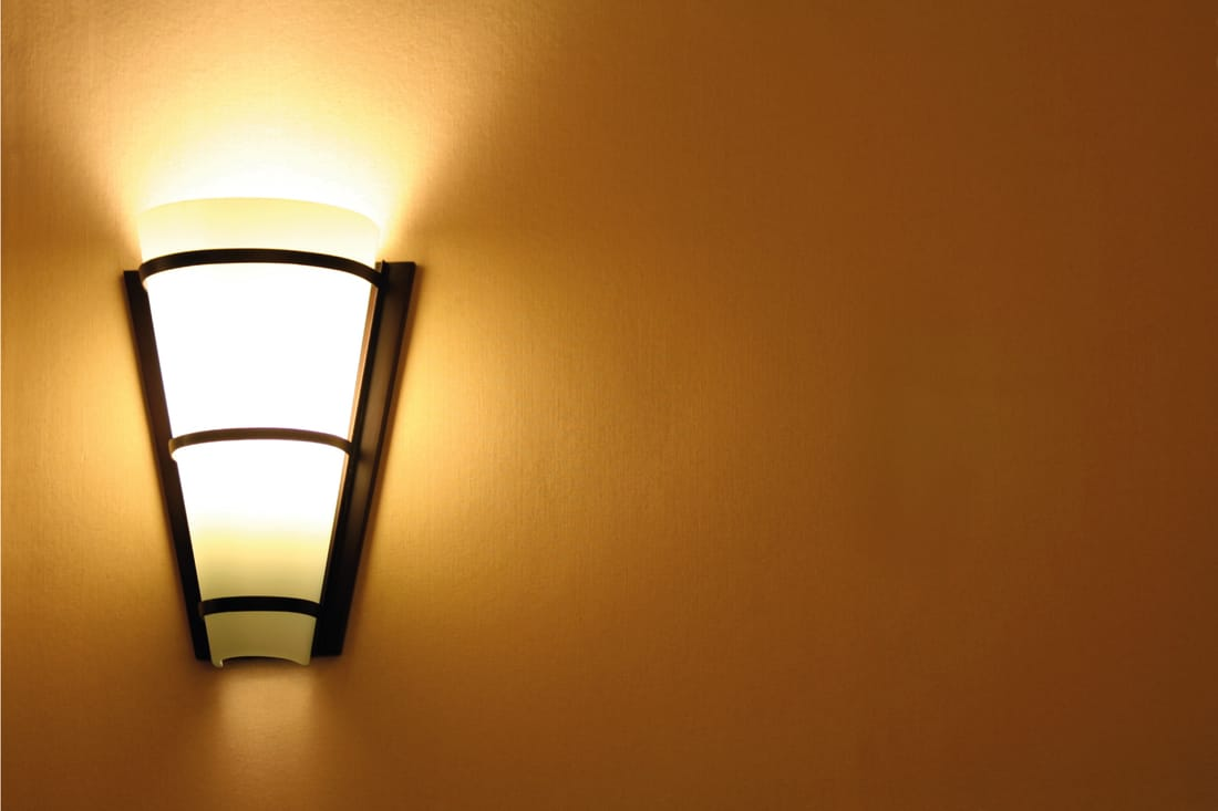 Lighted sconce wall lamp in brown wall background