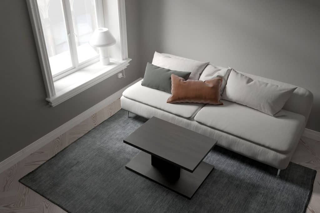 Living room with gray walls, gray couch and a rug with black rug on top of a patterned flooring