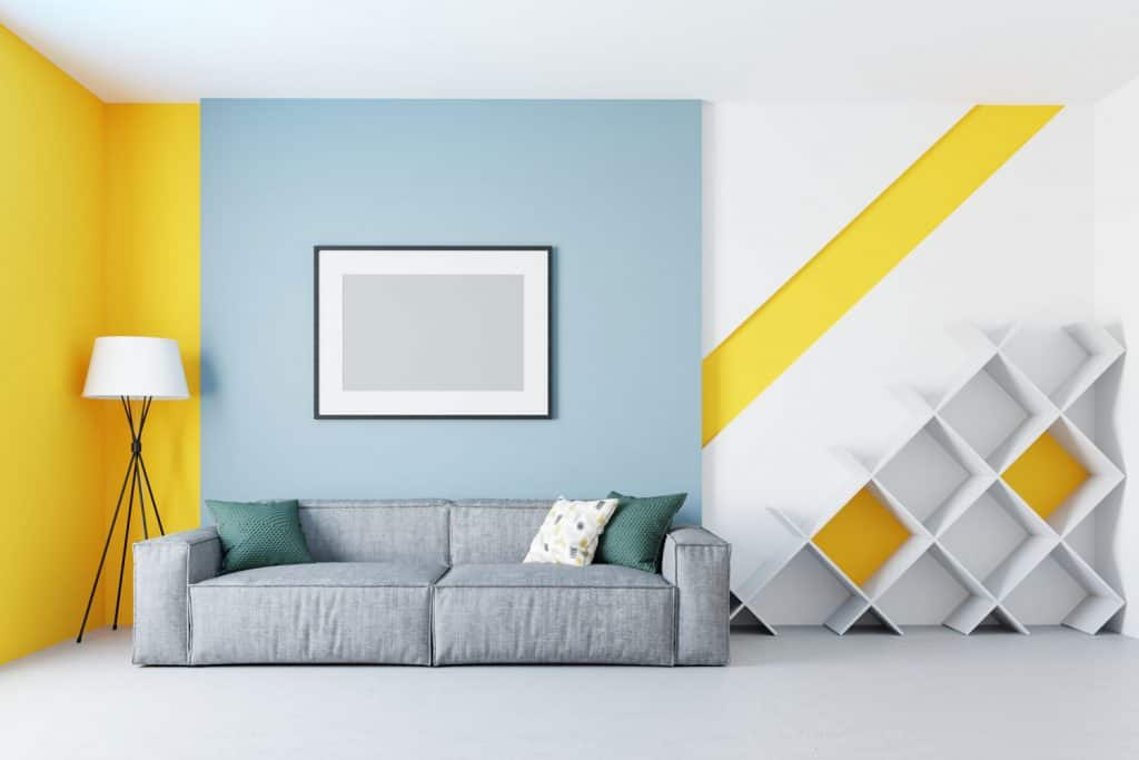 Living room with mixed colors and an accent wall with a yellow and light blue painting incorporated with a gray couch
