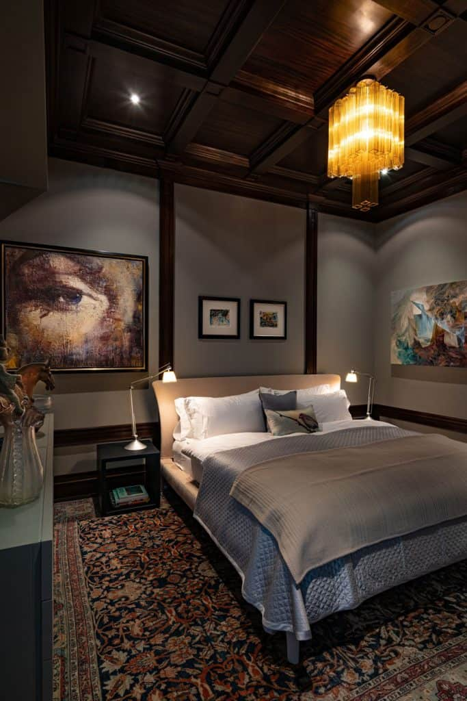 Luxurious dark classic themed bedroom with dark painted ceilings, a floral rug, and a cozy bed