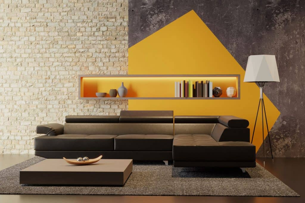 Luxurious living room with a sectional brown sofa, a concrete brick wall on the background painted with a mustard yellow