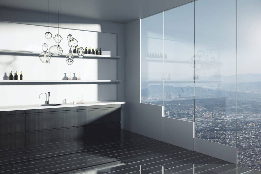 Luxurious modern kitchen area with a huge window and dark paneled cabinetry inside an apartment building