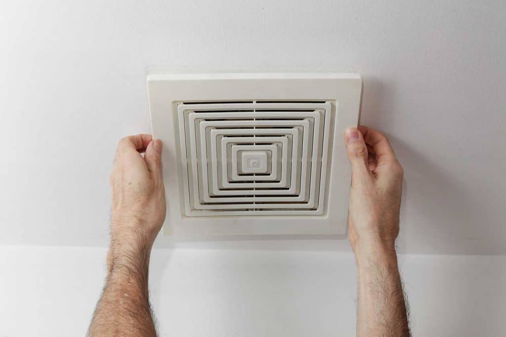 Man's hands removing air duct cover from ceiling