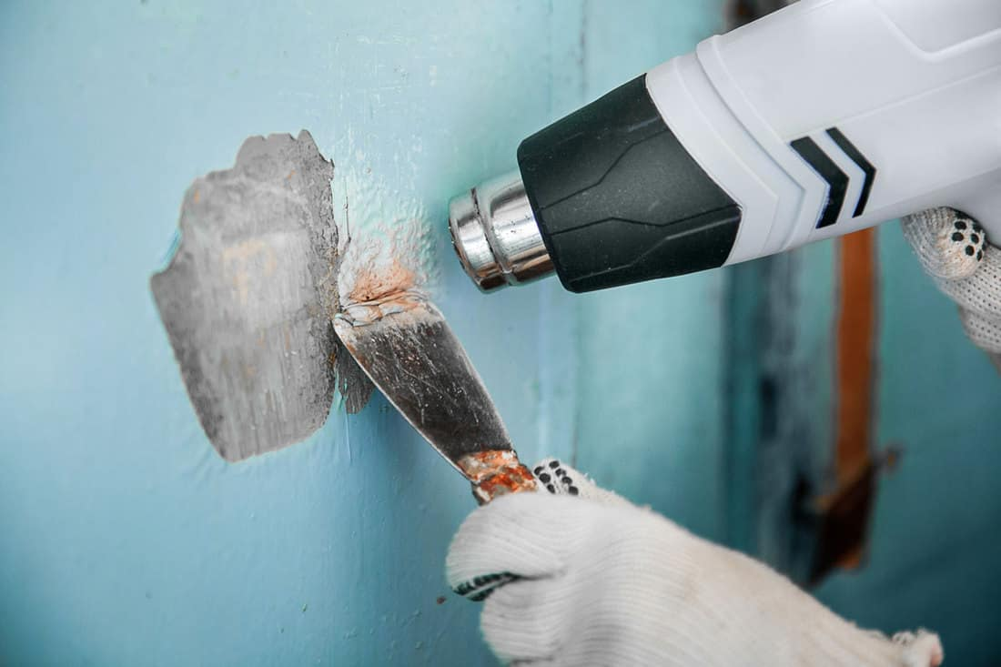 Master removes old paint from concrete wall with heat gun and scraper, How to Remove Paint From Concrete? [5 Simple Steps]