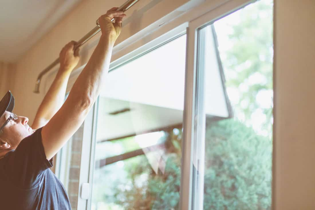 Mature Adult Male Installing Curtain Rods