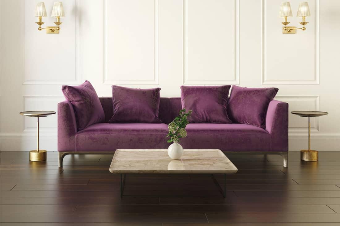 Modern chic classic luxury white European interior with violet velvet sofa on a dark wood floor