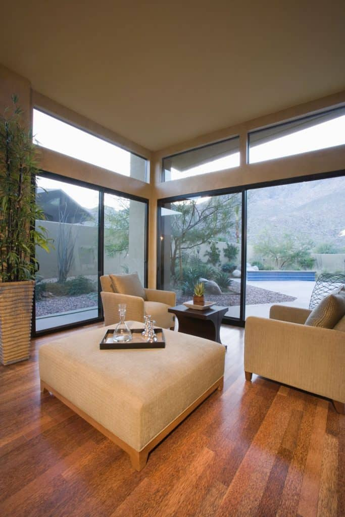 Modern contemporary living rom with glossy wooden flooring, cream ottoman and cream sofas